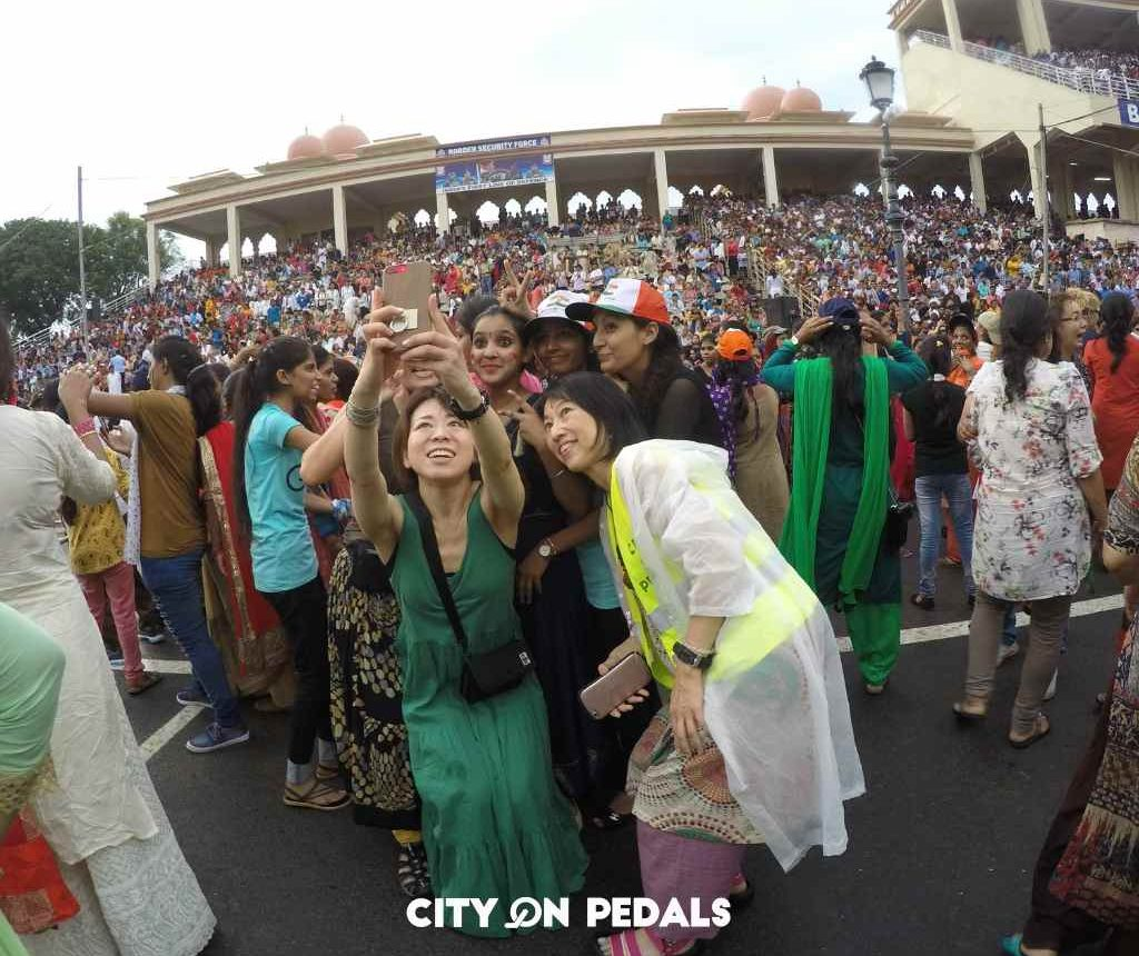 Group of Japanese travelers taking a selfie while dancing before the Wagah Border Ceremony