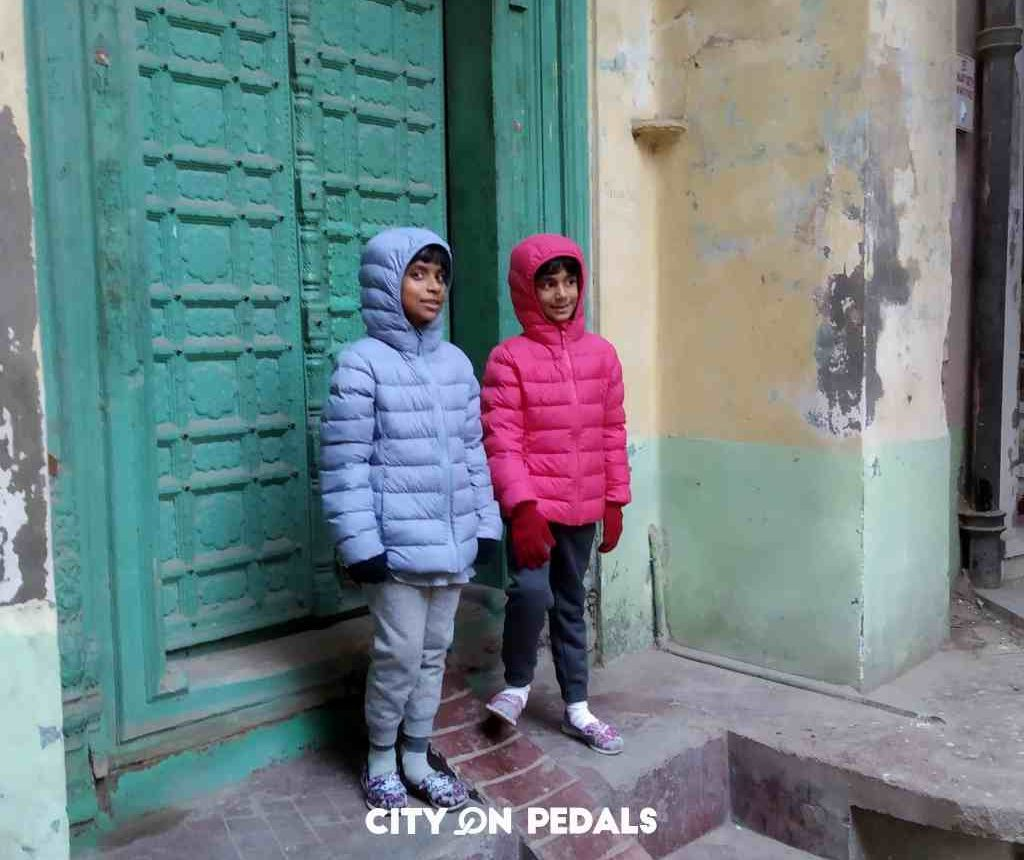 Kids taking a picture in front of an ancient house door during the Amritsar Heritage Walking Tour