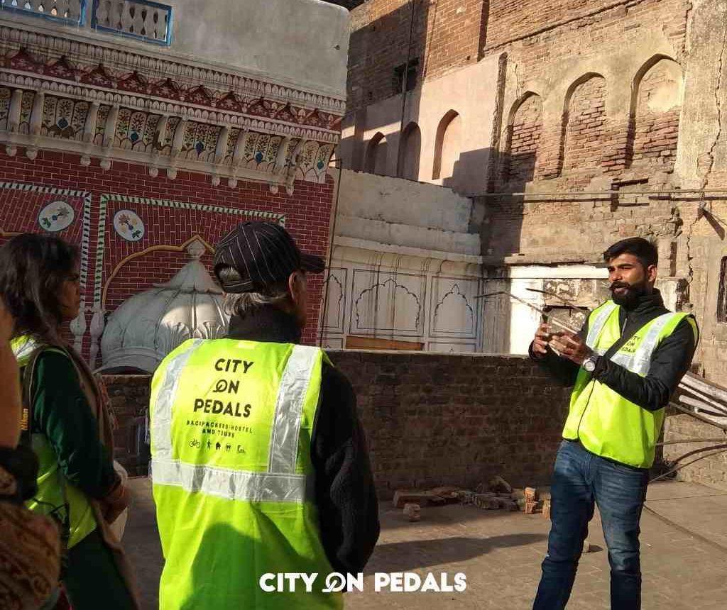 Tour guide explaining the significance of Thakurdwara Darianamal on the Amritsar Heritage Walking Tour