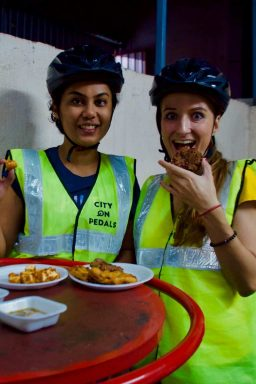 2 female travelers tasting pakora - street food of Amritsar